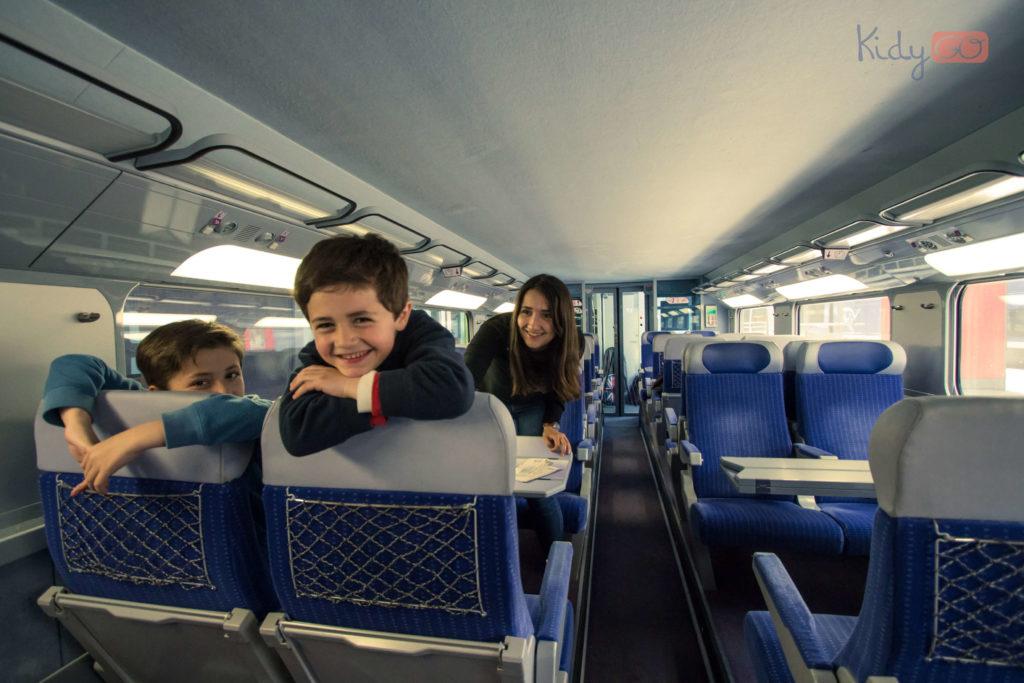 Photo de deux enfants avec leur accompagnatrice dans un train